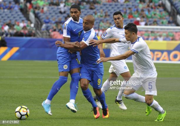 Michael Maria and Gino van Kessel of Curacao vie for control of the ball against Jesus Molina of El Salvador during the El Salvador vs Curacao...
