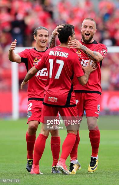 MIchael Marrone and Daniel Adlung of Adelaide celebrate with Nikola Mileusnic after he scored the first goal during the round six ALeague match...