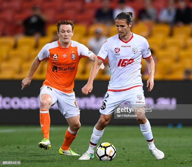 Michael Marrone of Adelaide United and Corey Brown of the Roar contest the ball during the round two ALeague match between the Brisbane Roar and...