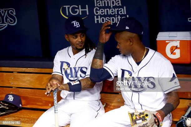Michael Martinez of the Tampa Bay Rays sits with new teammate Tim Beckham as they sit in the dugout before the start of a game against the New York...