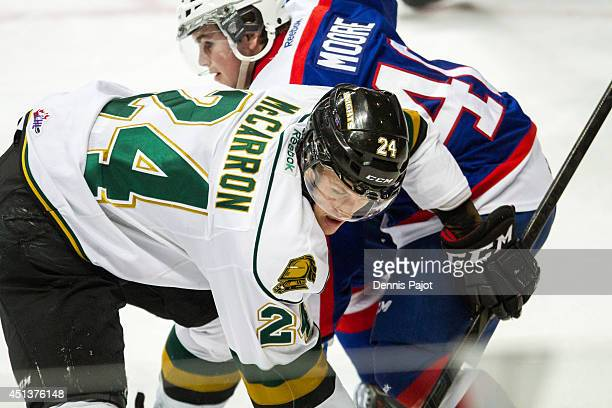 Michael McCarron of the London Knights battles for the puck on a faceoff against Ryan Moore of the Windsor Spitfires in Game 3 of their OHL...