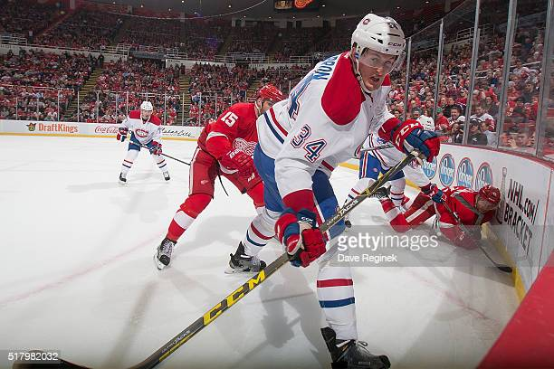 Michael McCarron of the Montreal Canadiens battles in the corner for the puck with Luke Glendening of the Detroit Red Wings during an NHL game at Joe...