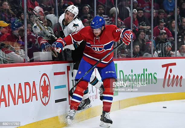 Michael McCarron of the Montreal Canadiens checks Justin Braun of the San Jose Sharks in the NHL game at the Bell Centre on December 16 2016 in...