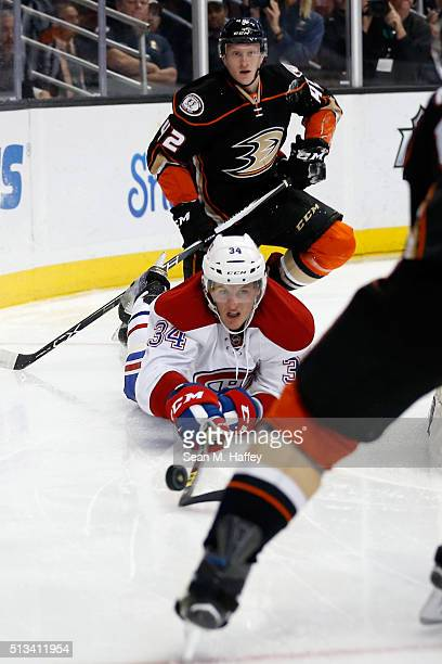 Michael McCarron of the Montreal Canadiens lunges for a loose puck after being hit by Josh Manson of the Anaheim Ducks during the second period of a...