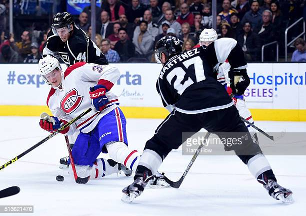Michael McCarron of the Montreal Canadiens plays the puck from his knees as Vincent Lecavalier and Alec Martinez of the Los Angeles Kings defend...