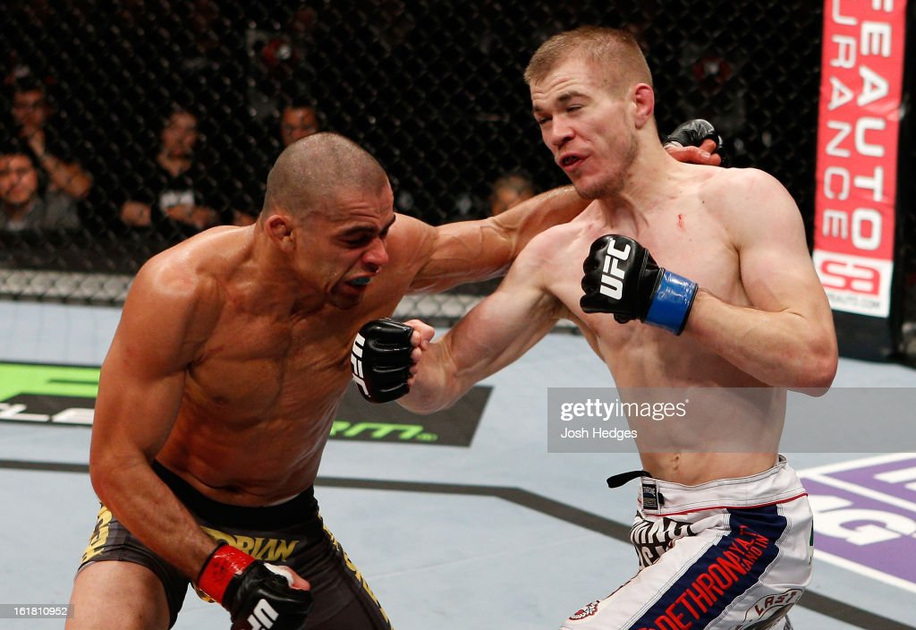 Michael McDonald punches Renan Barao in their interim bantamweight title fight during the UFC on Fuel TV event on February 16, 2013 at Wembley Arena in London, England.