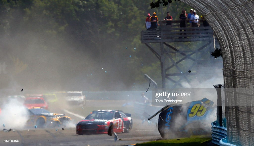 Michael McDowell, driver of the #95 K-Love Ford, and Ryan Newman, driver of the #31 Caterpillar Chevrolet, are involved in an on-track incident during the NASCAR Sprint Cup Series Cheez-It 355 at Watkins Glen International on August 10, 2014 in Watkins Glen, New York. The incident caused a red-flag period for repairs to a section of armco barrier.