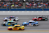 Michael McDowell driver of the KLove Radio Ford Trevor Bayne driver of the AdvoCare Ford and Joey Logano driver of the Shell Pennzoil Ford lead...