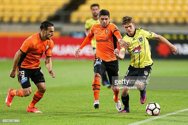 Michael McGlinchey of the Phoenix attempts to evade the defence of Jack Hingert and Dimitri Petratos of the Roar during the round 16 ALeague match...