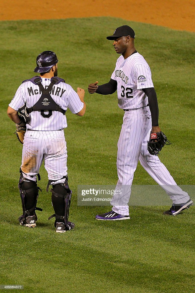 Michael McKenry #8 of the Colorado Rockies and LaTroy Hawkins #32 celebrate their 10-4 win against the Los Angeles Dodgers at Coors Field on September 16, 2014 in Denver, Colorado.