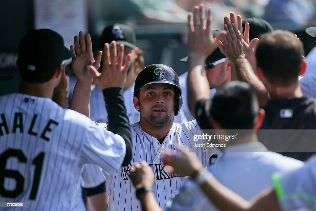 Michael McKenry #8 of the Colorado Rockies celebrates in the dugout after scoring during the seventh inning against the Milwaukee Brewers at Coors Field on June 20, 2015 in Denver, Colorado. The Rockies defeated the Brewers 5-1.
