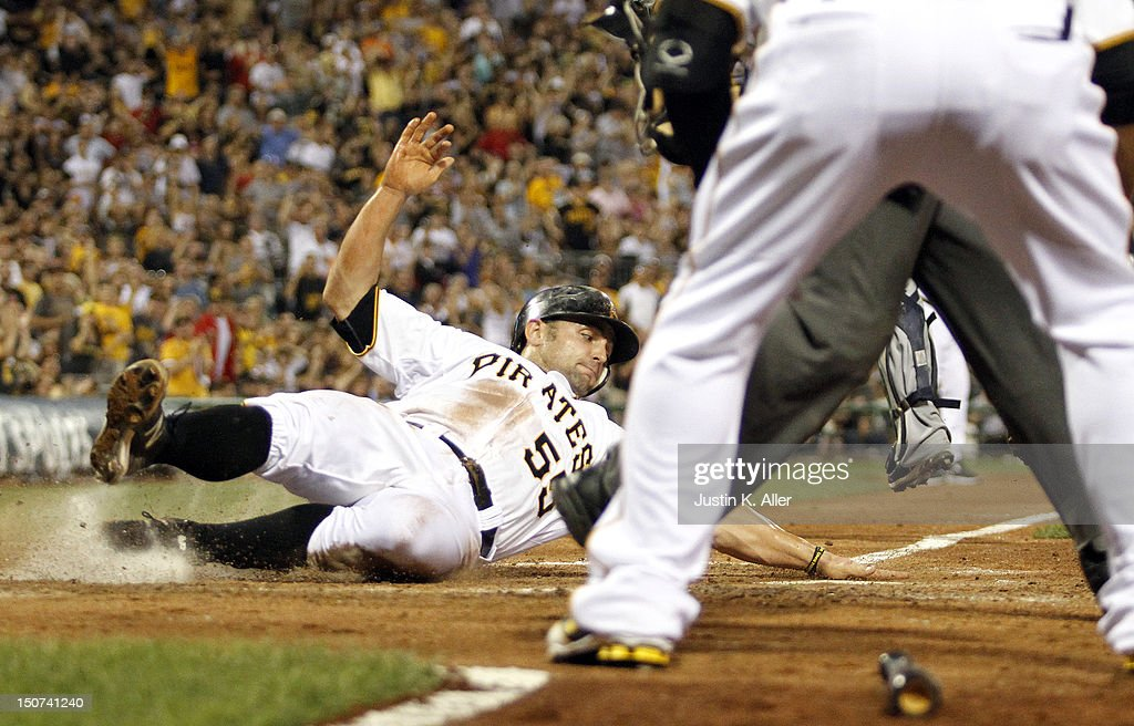 Michael McKenry #55 of the Pittsburgh Pirates slides safe into home on a RBI single by Jeff Karstens #27 (not pictured) against the Milwaukee Brewers during the game on August 25, 2012 at PNC Park in Pittsburgh, Pennsylvania.