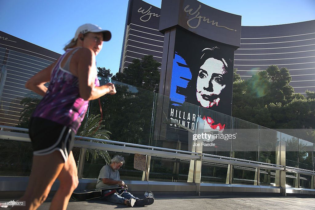 Michael McLean sets up to play his guitar for money near a billboard showing a picture of Democratic Presidential candidate Hillary Clinton...