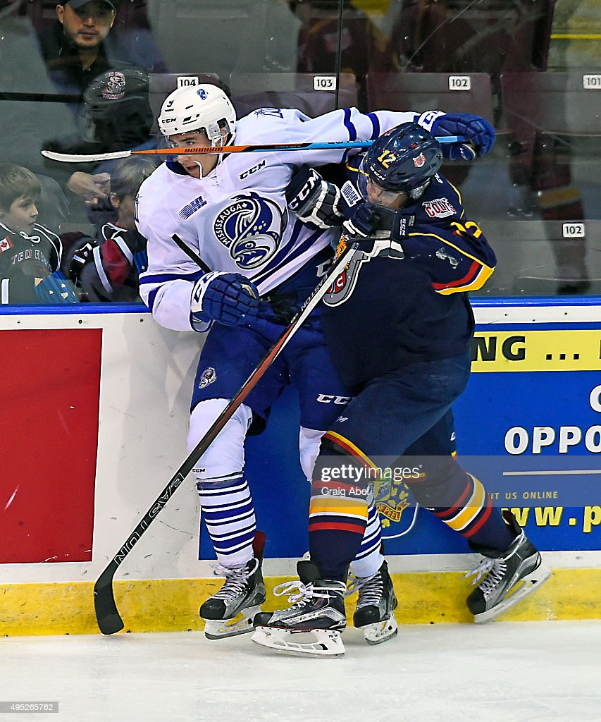 Michael McLeod #9 of the Mississauga Steelheads gets tangled up with Kevin Labanc #12 of the Barrie Colts during OHL game action on November 1, 2015 at the Hershey Centre in Mississauga, Ontario, Canada.