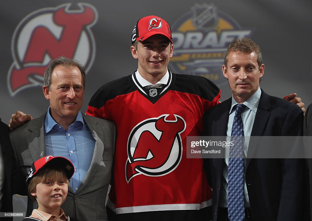 Michael McLeod stands onstage with team personnel after being selected 12th overall by the New Jersey Devils during round one of the 2016 NHL Draft at First Niagara Center on June 24, 2016 in Buffalo, New York.