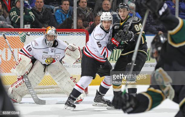 Michael McNiven and Sean Durzi of the Owen Sound Attack get set to face an incoming shot along with Alex Formenton of the London Knights during an...