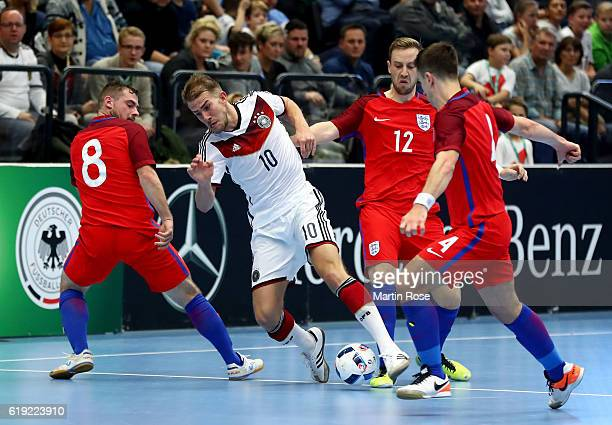 Michael Meyer of Germany and Luke Ballinger and Stuart Cook of England battle for the ball during the Futsal International Friendly match between...