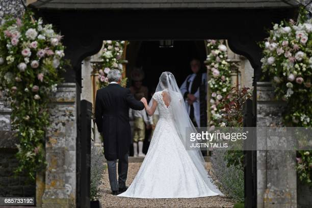 TOPSHOT Michael Middleton walks with his daughter Pippa Middleton as they arrive for her wedding to James Matthews at St Mark's Church in Englefield...