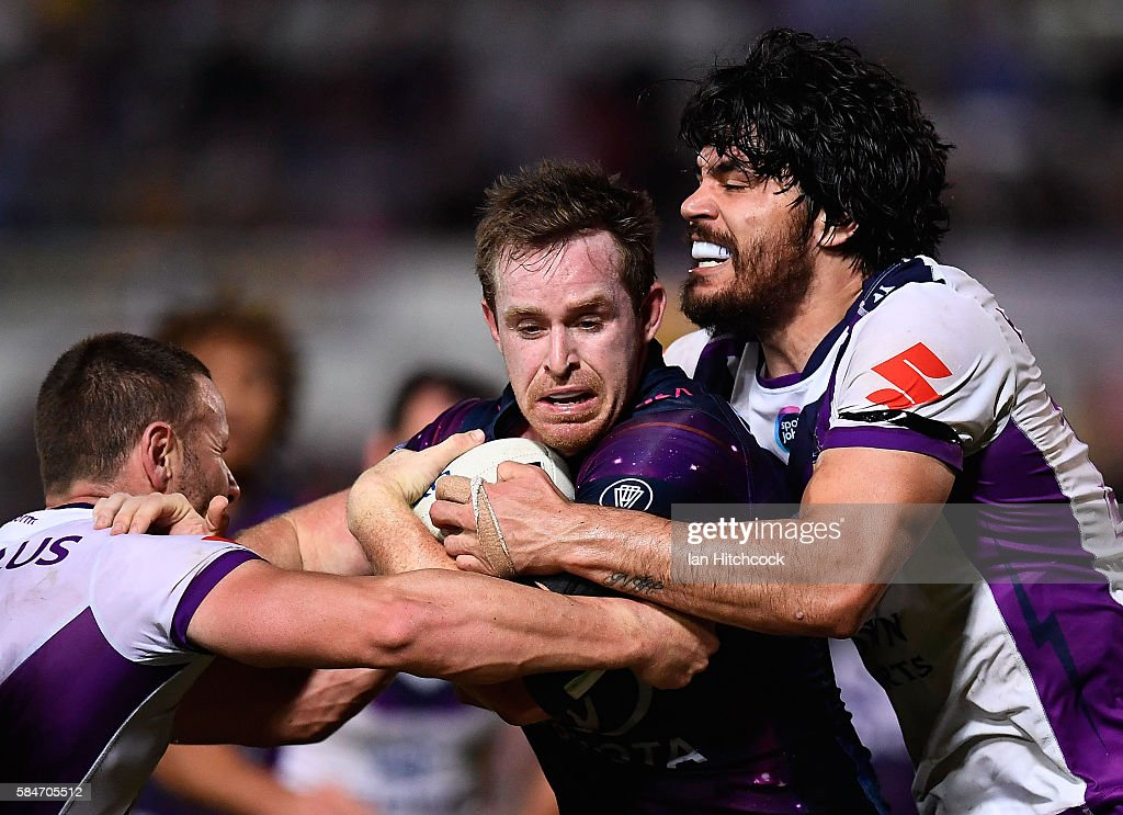 Michael Morgan of the Cowboys is tackled by Tohu Harris of the Storm during the round 21 NRL match between the North Queensland Cowboys and the Melbourne Storm at 1300SMILES Stadium on July 30, 2016 in Townsville, Australia.