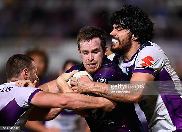 Michael Morgan of the Cowboys is tackled by Tohu Harris of the Storm during the round 21 NRL match between the North Queensland Cowboys and the...