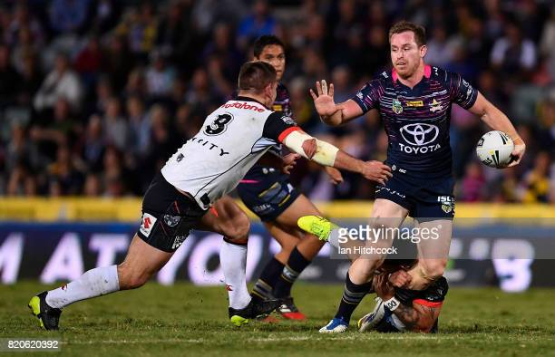 Michael Morgan of the Cowboys makes a break past Issac Luke and Jacob Lillyman of the Warriors during the round 20 NRL match between the North...
