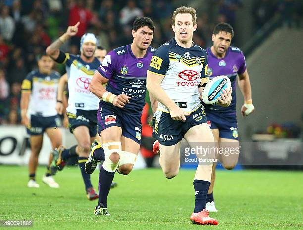 Michael Morgan of the Cowboys runs away to score a try as Johnathan Thurston of the Cowboys celebrates during the NRL Second Preliminary Final match...