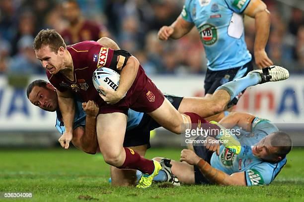 Michael Morgan of the Maroons is tackled during game one of the State Of Origin series between the New South Wales Blues and the Queensland Maroons...