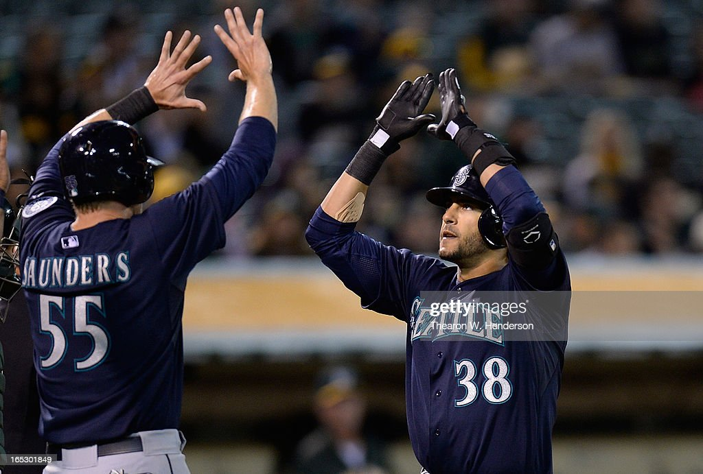 Michael Morse #38 and Michael Saunders #55 of the Seattle Mariners celebrate after Morse hit a three-run home run against the Oakland Athletics in the third inning at O.co Coliseum on April 2, 2013 in Oakland, California.