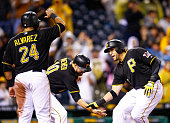 Michael Morse of the Pittsburgh Pirates is congratulated by Neil Walker and Pedro Alvarez after hitting a grand slam against the Milwaukee Brewers in...