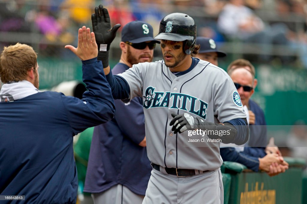 Michael Morse #38 of the Seattle Mariners is congratulated by teammates in the dugout after hitting a home run against the Oakland Athletics during the sixth inning at O.co Coliseum on April 4, 2013 in Oakland, California. The Oakland Athletics defeated the Seattle Mariners 8-2.