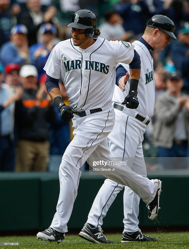 Michael Morse #38 of the Seattle Mariners is congratulated by third base coach Jeff Datz #43 on a game-winning solo home run in the eighth inning against the Los Angeles Angels of Anaheim at Safeco Field on April 28, 2013 in Seattle, Washington. The Mariners defeated the Angels 2-1.