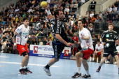 Michael Mueller of RheinNeckar Loewen is challenged by Nenad Vuckovic and Felix Danner of Melsungen during the Toyota Handball Bundesliga match...