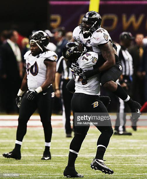 Michael Oher and Arthur Jones of the Baltimore Ravens react after the San Francisco 49ers couldn't convert on a fourth down play in the final two...