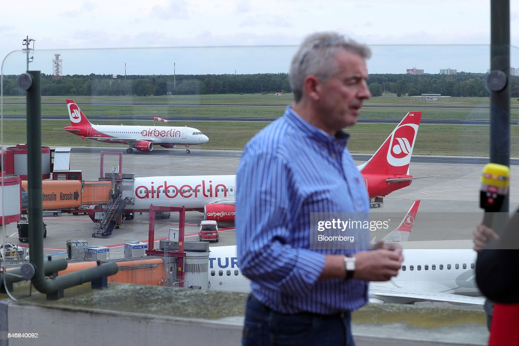 Michael O'Leary, chief executive officer of Ryanair Holdings Plc, speaks to a journalist following a news conference as Air Berlin Plc passenger jets stand on the tarmac beyond at Tegel airport in Berlin, Germany, on Thursday, Sept. 14, 2017. Ryanair Holdings Plcshares fell more than 4.4 percent after the European Unions top court ruled the airline could face employee lawsuits wherever cabin crew are based, paving the way for a flurry of claims outside of Ireland and a possible increase in employment costs. Photographer: Krisztian Bocsi/Bloomberg via Getty Images