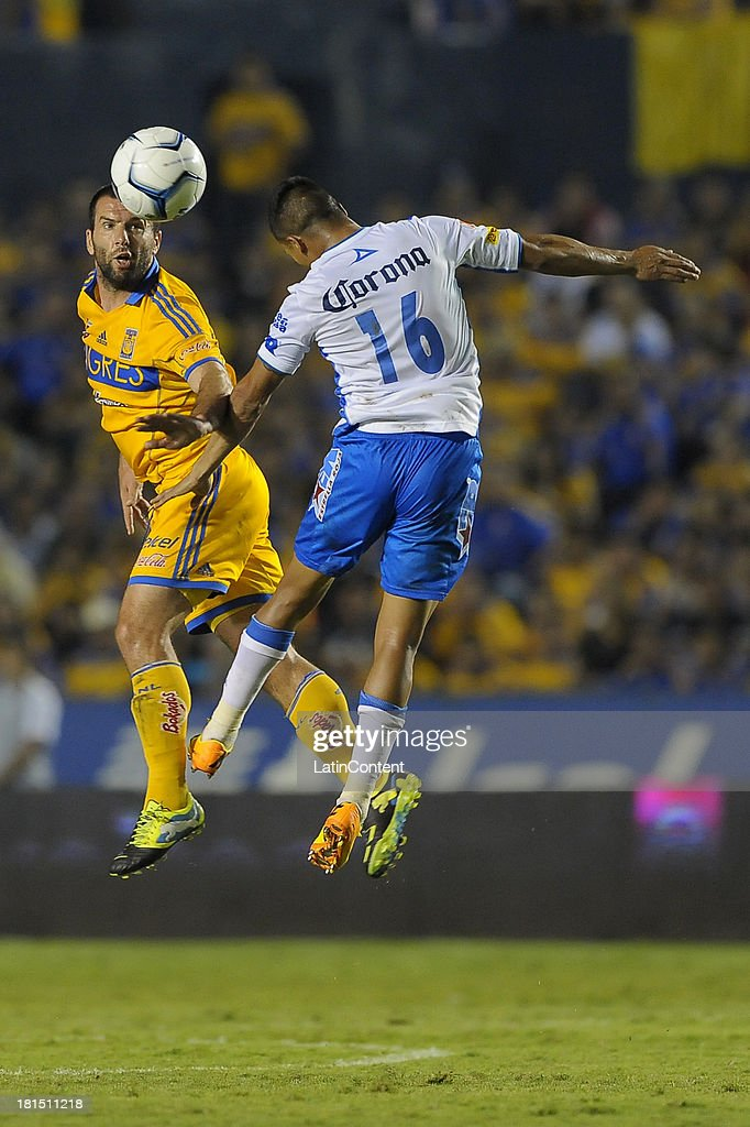 Michael Orozco of Puebla jumps for the ball with <a gi-track='captionPersonalityLinkClicked' href=/galleries/search?phrase=Emanuel+Villa&family=editorial&specificpeople=3061294 ng-click='$event.stopPropagation()'>Emanuel Villa</a> of Tigres in action during a match between Tigres UANL and Puebla FC as part of the Liga MX at Universitario stadium on September 21, 2013 in Monterrey, Mexico.