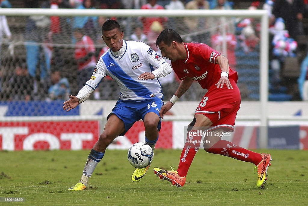 Michael Orozco (L) of Puebla struggles for the ball with <a gi-track='captionPersonalityLinkClicked' href=/galleries/search?phrase=Edgar+Benitez&family=editorial&specificpeople=3433635 ng-click='$event.stopPropagation()'>Edgar Benitez</a> (R) of Toluca during a match as part of Apertura 2013 Liga MX at Cuauhtemoc Stadium on September 14, 2013 in Puebla, Mexico.
