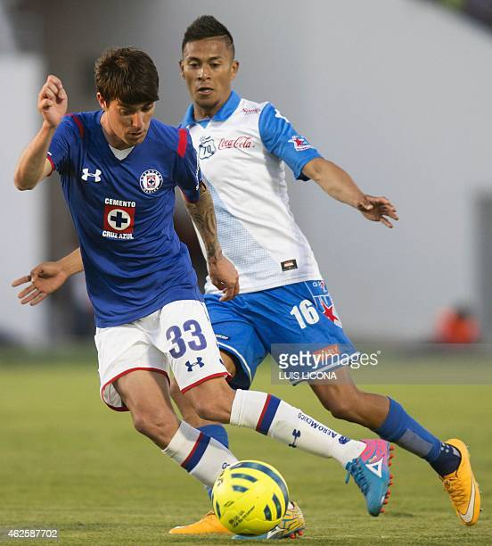 Michael Orozco of Puebla vies for the ball with Mauro Formica of Cruz Azul during their Mexican Clausura tournament football match at the Cuauthemoc...