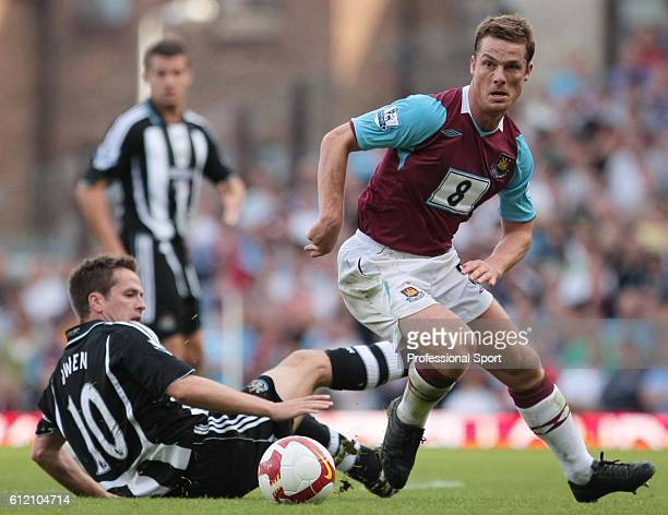 Michael Owen of Newcastle slides in on Scott Parker of West Ham United during the Barclays Premier League match between West Ham United and Newcastle...