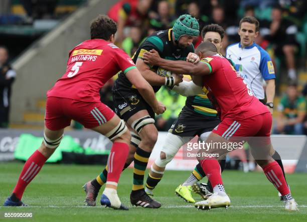 Michael Paterson of Northampton is tackled by Kyle Sinckler and Charlie Matthews during the Aviva Premiership match between Northampton Saints and...