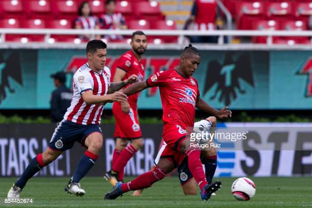 Michael Perez of Chivas fights for the ball with Pedro Aquino of Lobos during the 11th round match between Chivas and Lobos BUAP as part of the...