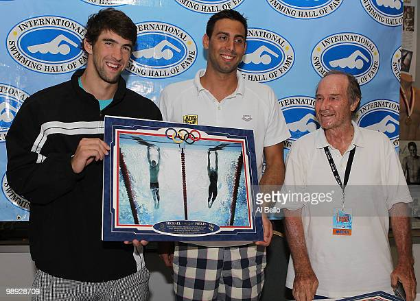 Michael Phelps and Milorad Cavic hold up their famous 100m Butterfly photo finish taken by Sports Illustrated photographer Heinz Kluetmeir which will...