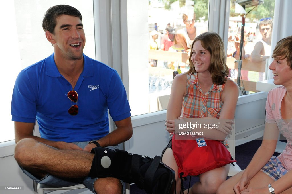 Michael Phelps chat with the winner competition (C) during their visit to the Speedo Store during the Barcelona 2013 World Swimming Championships on July 28, 2013 in Barcelona, Spain.