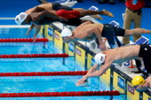 Michael Phelps dives of off the starting block as he competes in preliminary heat 13 of the Men's 100 m Butterfly during Day Six of the 2012 US...