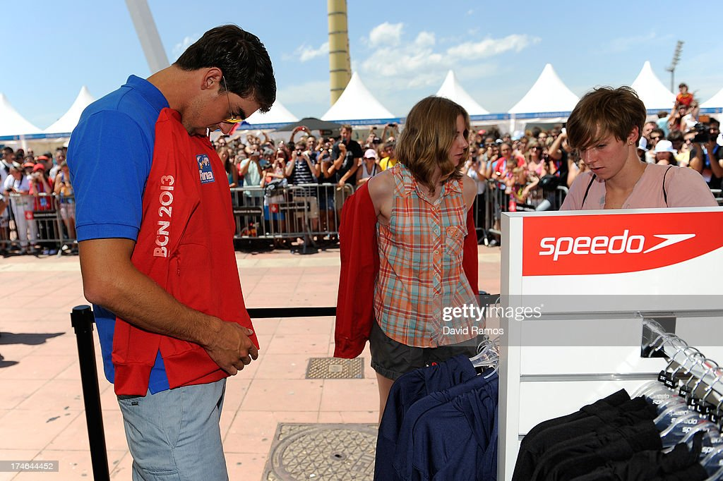 Michael Phelps helps to the winner competition (C) during their shooping activity at the Speedo Store during the Barcelona 2013 World Swimming Championships on July 28, 2013 in Barcelona, Spain.