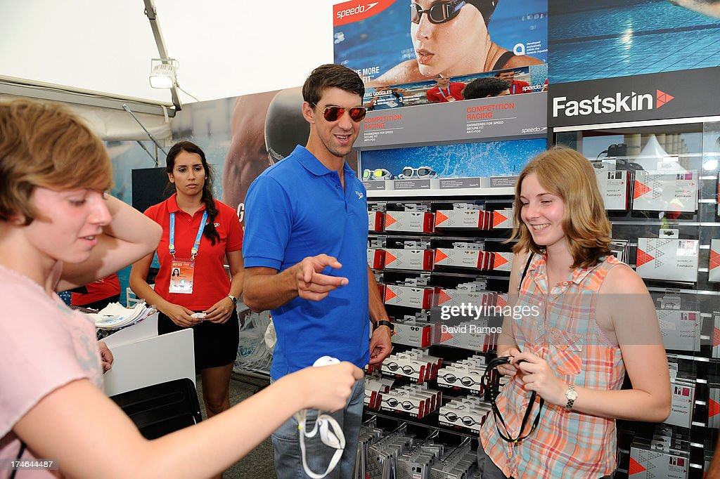 Michael Phelps helps to the winner competition (R) during their shooping activity at the Speedo Store during the Barcelona 2013 World Swimming Championships on July 28, 2013 in Barcelona, Spain.