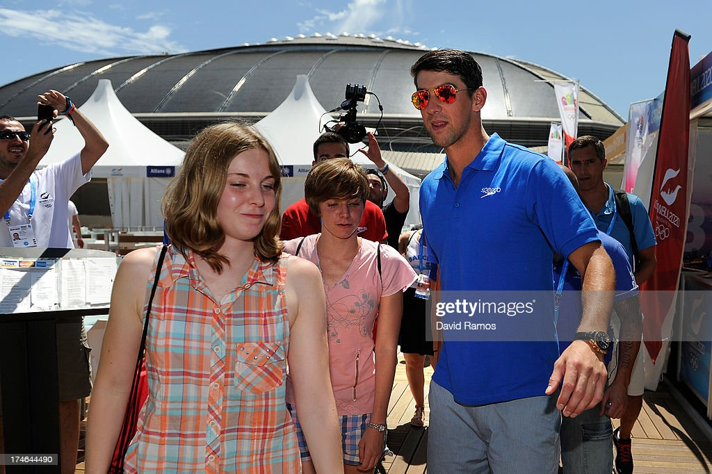Michael Phelps helps to the winner competition (L) during their shooping activity at the Speedo Store during the Barcelona 2013 World Swimming Championships on July 28, 2013 in Barcelona, Spain.