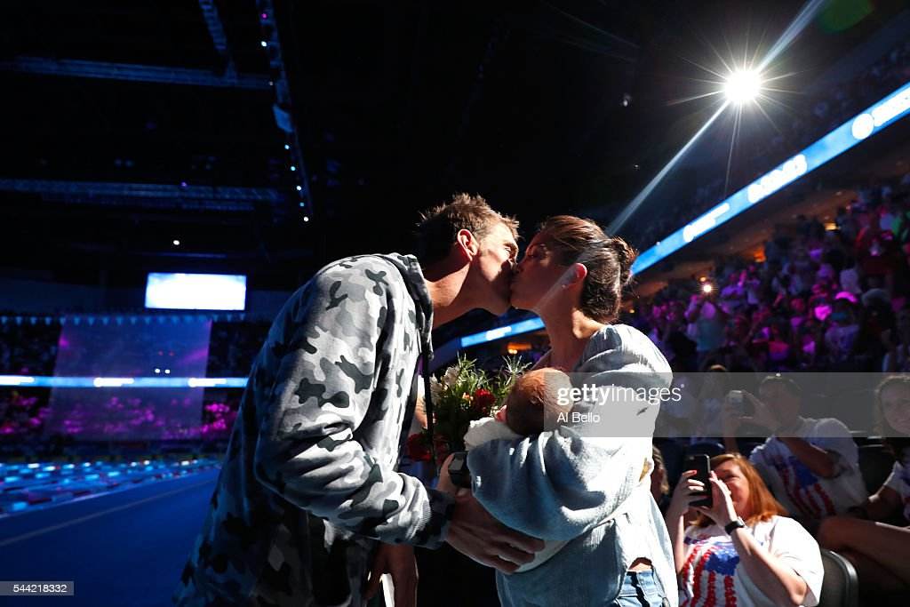 Michael Phelps of the United States celebrates with his fiance Nicole Johnson and their son Boomer after finishing first in the final heat for the...