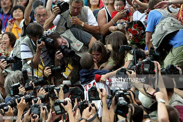 Michael Phelps of the United States greets his family sister's Whitney and Hilary and mother Debbie in the stands as he is surrounded by...