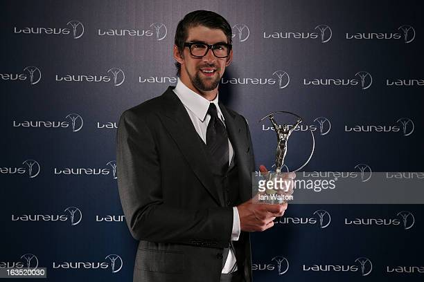 Michael Phelps poses with the award for Laureus Academy Exceptional Achievement Award in the winners studio during the 2013 Laureus World Sports...