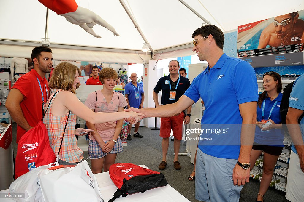 Michael Phelps shakes hands with the winner competition during their visit to the Speedo Store during the Barcelona 2013 World Swimming Championships on July 28, 2013 in Barcelona, Spain.